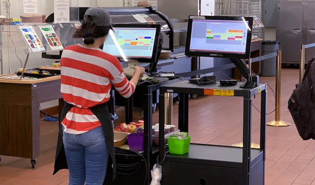 Worker operating a POS terminal attached to a rolling cart